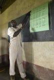 英国音节的老师对孩子的蓝色制服的在书桌在察沃国家公园附近,肯尼亚,非洲后的学校 免版税库存图片