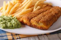英国食物:在板材的油煎的鱼片和芯片特写镜头 免版税库存图片