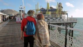 英国,布赖顿 可爱的青年人沿码头走 青年人举行手 在海洋海岸 股票录像