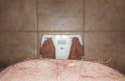 英尺长毛的人伸出缩放比例胃 库存图片