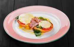 英式早餐炸面包多士用鸡蛋、菠菜、蕃茄、无盐干酪乳酪和火腿在板材在黑暗的木背景 免版税图库摄影