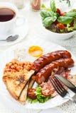 英式早餐用烟肉、香肠、煎蛋和被烘烤的豆 免版税库存图片