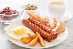 英式早餐用熏制的香肠、炒蛋、烟肉、蘑菇、多士和豆 奶茶 在白色pla的早餐 免版税库存图片