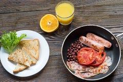 英式早餐用香肠、被烘烤的蕃茄、豆和toa 免版税库存照片