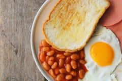 英式早餐:煎蛋、烟肉、豆和多士 免版税库存照片