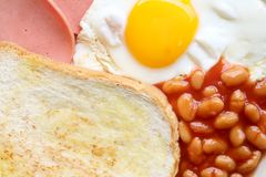 英式早餐:煎蛋、烟肉、豆和多士 免版税库存图片