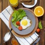 英式早餐:煎蛋,汁液,西红柿,莴苣,五谷面包,调味汁 免版税库存图片