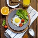 英式早餐:煎蛋,汁液,西红柿,莴苣,五谷面包,调味汁 免版税库存照片