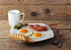英式早餐-炒蛋,烟肉,油煎了多士和茶 免版税库存照片