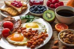 英式早餐-煎蛋、豆、蕃茄、咖啡、烟肉和多士与坚果,新鲜水果和莓果 库存照片