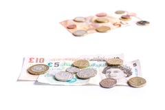 英磅纸币和硬币和欧洲纸币和硬币在白色 图库摄影