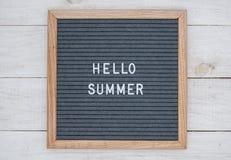 英语发短信给你好在一个信件板的夏天在灰色背景的白色信件 免版税库存图片