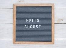 英语发短信给你好在一个信件板的8月在灰色背景的白色信件 库存图片