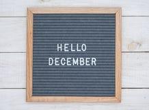 英语发短信给你好在一个信件板的12月在灰色背景的白色信件 库存照片
