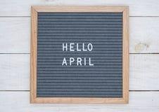 英语发短信给你好在一个信件板的4月在灰色背景的白色信件 免版税图库摄影