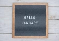 英语发短信给你好在一个信件板的1月在灰色背景的白色信件 免版税库存照片