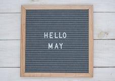 英语发短信给你好在一个信件板的5月在灰色背景的白色信件 免版税库存图片