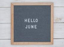 英语发短信给你好在一个信件板的6月在灰色背景的白色信件 图库摄影