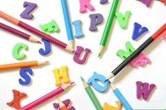 英语字母表的颜色信件 在他们旁边是色的铅笔 顶视图 教的孩子 图库摄影
