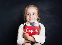 英语概念 与书微笑的逗人喜爱的儿童学生 免版税库存图片