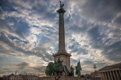 英雄摆正Hosok Tere在布达佩斯,匈牙利,在日落,当游人攀登主要雕象和专栏 免版税库存照片