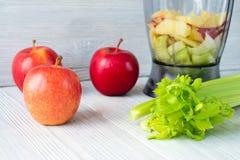 苹果、一束芹菜和在白色桌上的一台食品加工器 库存照片