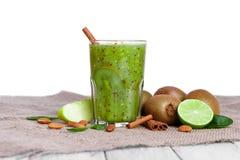 从苹果、猕猴桃和石灰的一个有机鲜绿色的饮料在一个棕色袋子,隔绝在白色背景 复制空间 库存照片