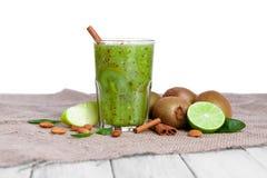 从苹果、猕猴桃和石灰的一个有机鲜绿色的饮料在一个棕色袋子,隔绝在白色背景 复制空间 免版税库存图片