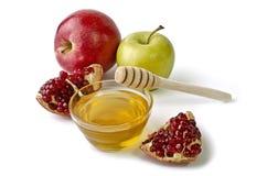 苹果、石榴和碗蜂蜜 免版税库存图片