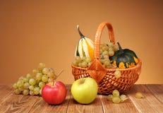 苹果、葡萄和装饰南瓜在柳条筐 库存图片