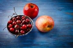 苹果和一个碗用一棵樱桃在一张蓝色桌上 库存图片