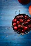 苹果和一个碗用一棵樱桃在一张蓝色桌上 免版税库存图片