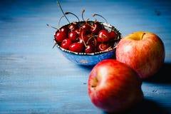 苹果和一个碗用一棵樱桃在一张蓝色桌上 库存照片