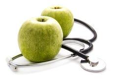 苹果和听诊器背景 图库摄影
