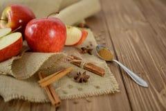 苹果和桂香在黄麻织品和黑暗的木背景 库存图片