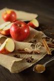 苹果和桂香在黄麻织品和黑暗的木背景 库存照片