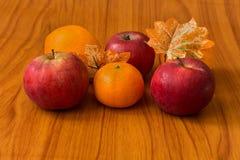 苹果和桔子在棕色背景 免版税库存图片