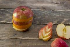 苹果和桔子的混合在一张木书桌上 库存照片