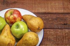 苹果和梨在土气木桌上 免版税库存照片