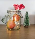 苹果和棒棒糖看法在一个瓶子有圣诞灯和树小雕象的 图库摄影