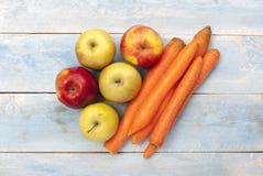 苹果和红萝卜在一个蓝色木板 库存图片