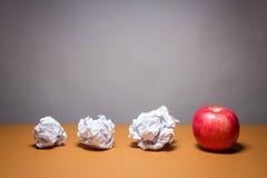 苹果和被弄皱的纸 企业失望、工作压力和不合格的检查概念 免版税库存图片
