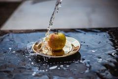 苹果在水中放出在板材的身分户外 免版税库存照片