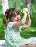 苹果女孩绿色室外的一点 免版税库存照片