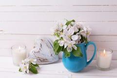苹果树开花,心脏和蜡烛在白色木背景 库存照片