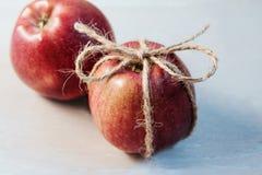 苹果栓了与在轻的背景的一条绳索 库存照片