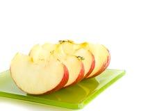 苹果片断在绿色盘的 库存照片