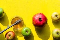苹果用蜂蜜,在一张黄色桌上的石榴犹太新年特写镜头的 免版税库存图片