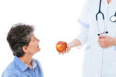 给苹果的有同情心的医生她不适的患者 免版税库存照片
