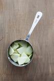 苹果立方体在一个量杯的 免版税库存图片